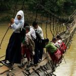 Bambini di Sumatra vanno a scuola guadando un fiume